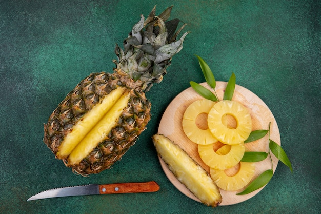 Top view of pineapple with one piece cut out from whole fruit and pineapple slices on cutting board with knife on green surface