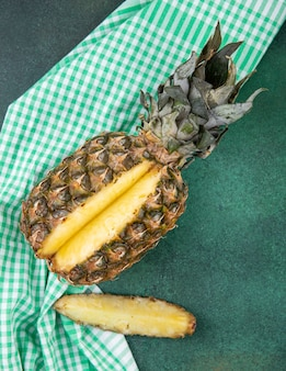 Top view of pineapple with one piece cut out from whole fruit on plaid cloth and green surface
