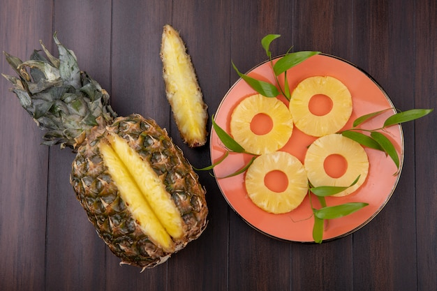 Top view of pineapple with one piece cut out from whole fruit with pineapple slices in plate on wooden surface