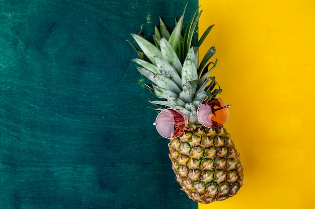 Top view of pineapple with red glasses