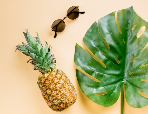Top view pineapple with sunglasses and leaf