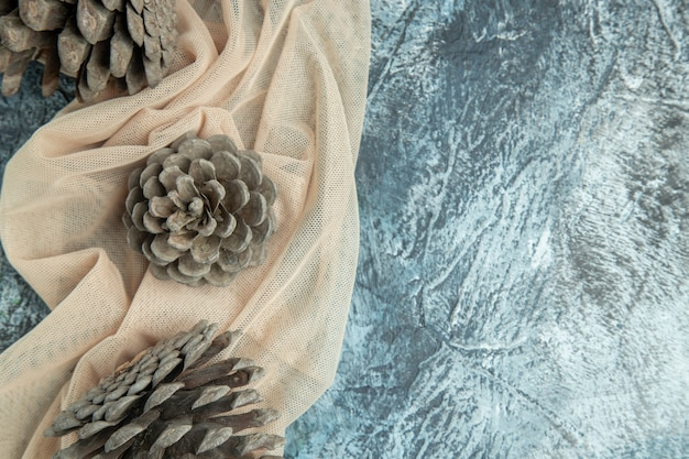 Top view pinecones on beige shawl on dark surface free space