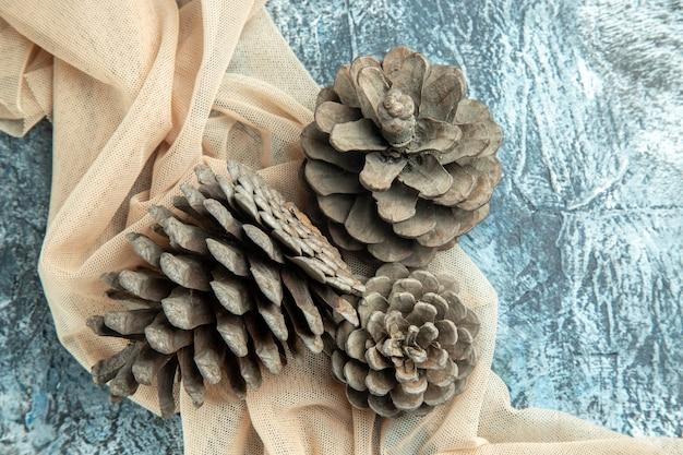 Top view pinecones on beige shawl on dark surface
