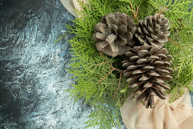 Top view pinecones pine branches on beige shawl on dark surface free space