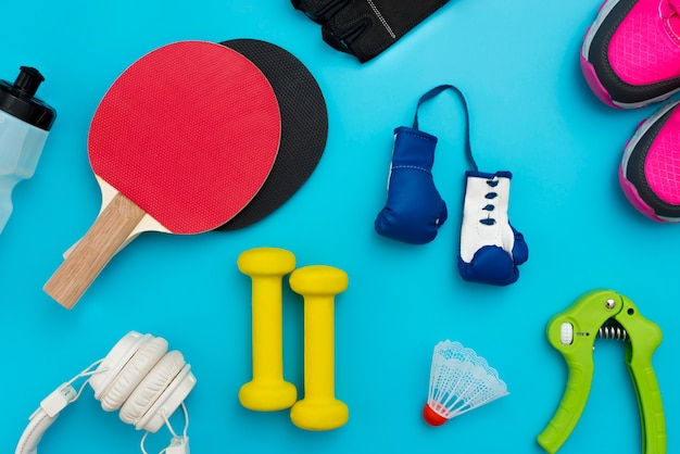 Top view of ping pong paddles with boxing gloves and sport essentials