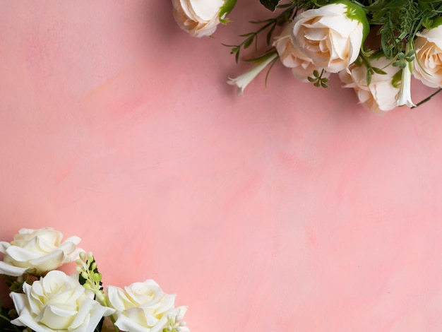 Top view pink background with white roses frame