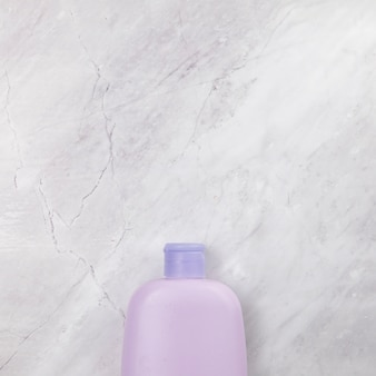 Top view of pink bottle on marble background