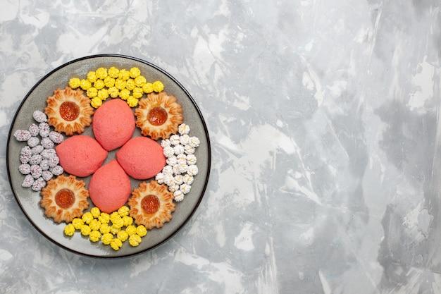 白い背景の上のプレートの中にキャンディーとクッキーが入った上面のピンクのケーキ甘い焼きケーキビスケットティーパイクッキー