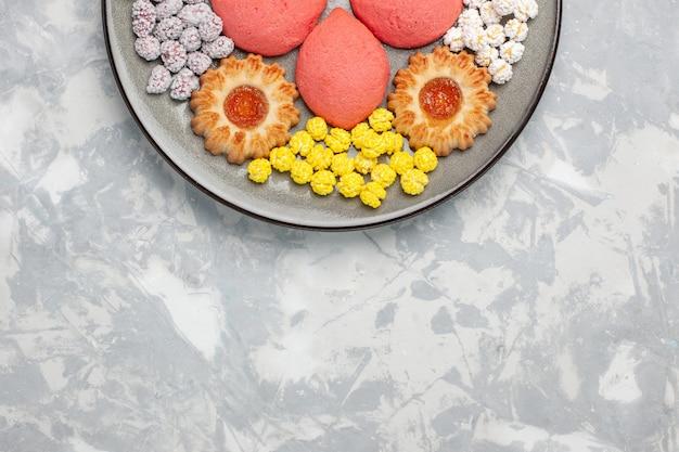 白い机の上のプレートの中にキャンディーとクッキーが入った上面のピンクのケーキ甘い焼きケーキビスケットティーパイクッキー