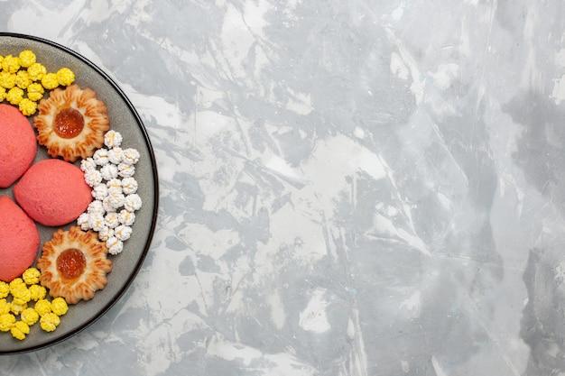 Вид сверху розовые торты с конфетами и печеньем внутри тарелки на белом столе, сладкая выпечка, бисквит, чай, пирог, печенье
