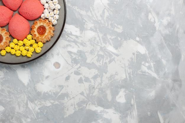 Vista dall'alto torte rosa con caramelle e biscotti all'interno della piastra sul pavimento bianco dolce cuocere il biscotto della torta del biscotto della torta del tè