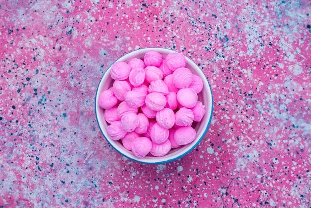 カラフルな背景キャンディシュガーグッドイカラーのプレート内のトップビューピンクキャンディー