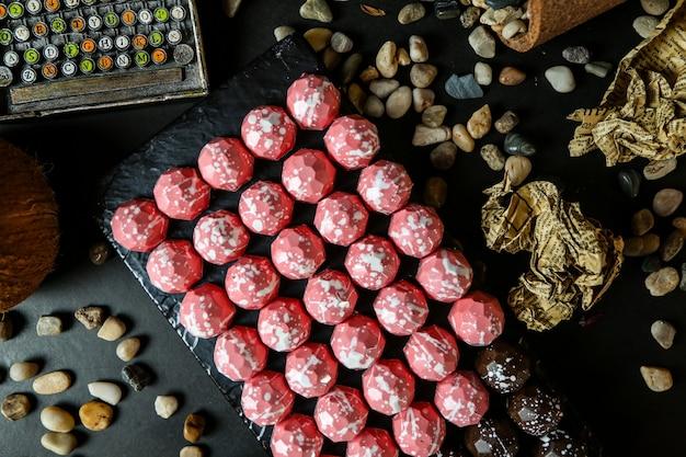 Vista dall'alto di cioccolatini rosa su un supporto con pietre