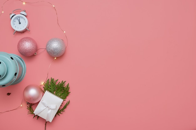 Top view of pink christmas balls and mint lamp on pink background