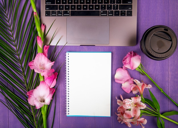 Top view of pink color gladiolus and roses with alstroemeria flowers arranged around a sketchbook laptop and a paper cup of coffee on purple background