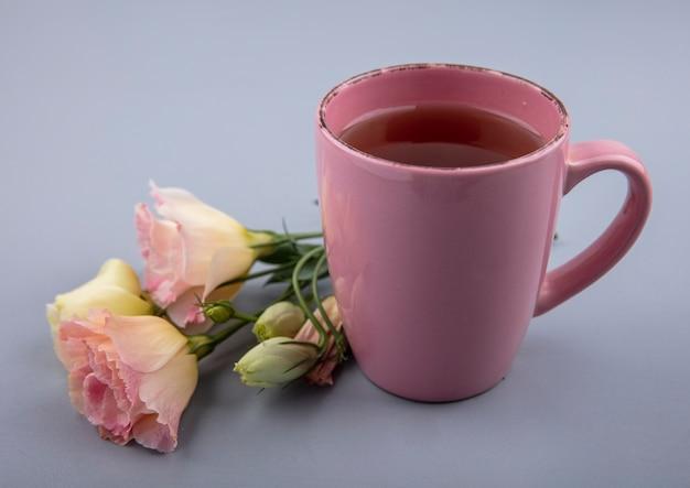Vista dall'alto di una tazza di tè rosa con fiori freschi su sfondo grigio