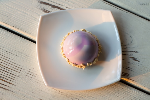 Top view of pink dessert. little cake on white plate. mousse cake with mirror glaze. sweet snack in the cafe.