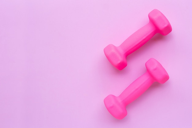 Top view of pink dumbbells isolated on pink background.