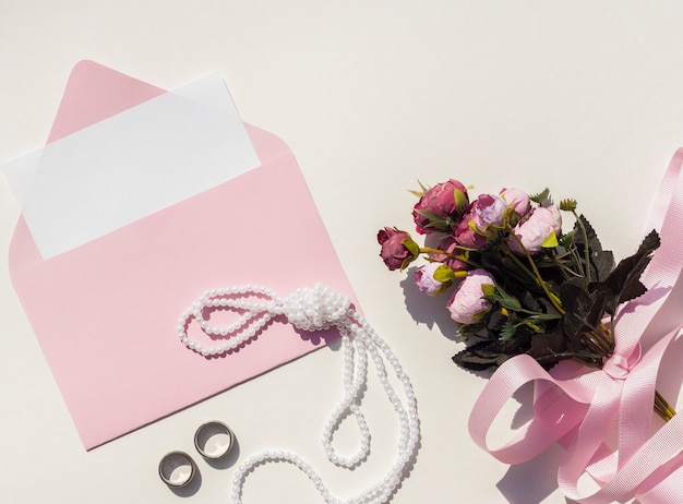 Top view pink envelope with wedding invitation next to bouquet of roses