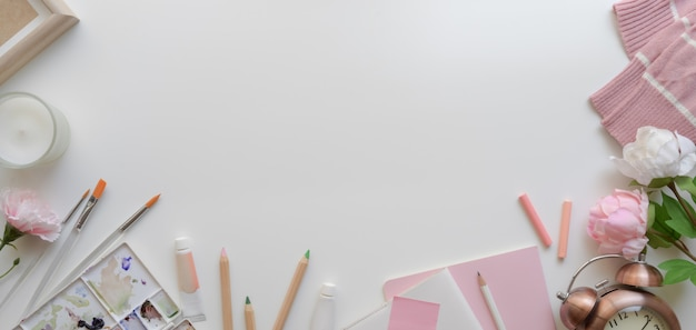 Top view of pink feminine artist workspace with copy space and painting tools