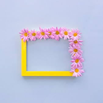 Top view of pink flowers arranged on yellow border photo frame over blue background