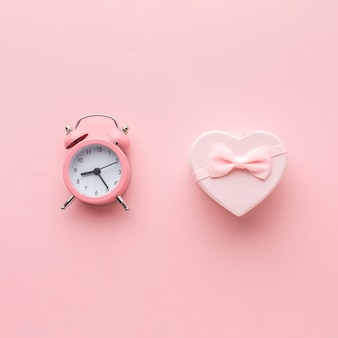 Top view of pink gift with clock