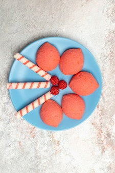 上面図白い背景の上のプレート内のピンクのジンジャーブレッドケーキビスケット甘いパイシュガークッキー
