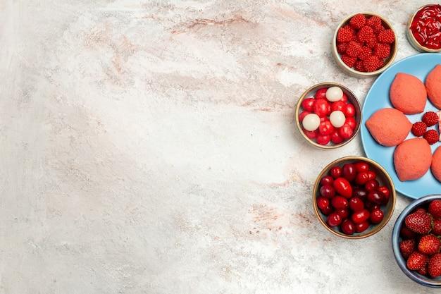 Вид сверху розовые пряники с фруктами и ягодами на белом фоне сахарный бисквитный пирог сладкий торт печенье