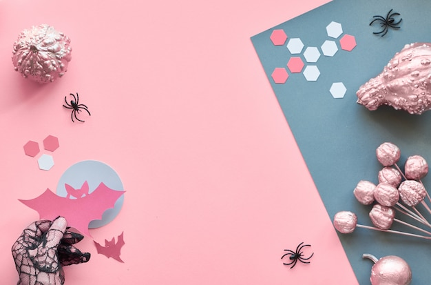 Top view on pink and grey split paper background with bats over red full moon, black spiders, paper hexagons. creative paper craft halloween flat lay with copy-space. hand in mesh glove holding bat.