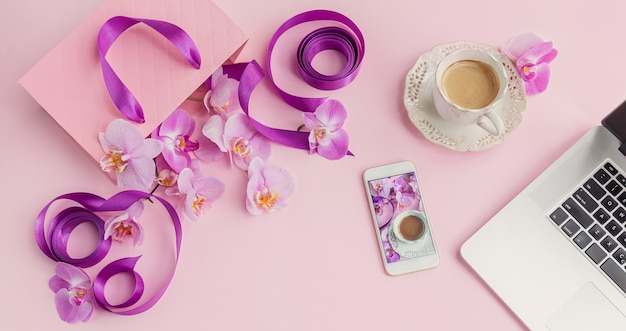 Top view of pink home office workspace with laptop, phone and coffee cup. social media flat lay with coffee, flowers and smartphone. female pink floral workplace