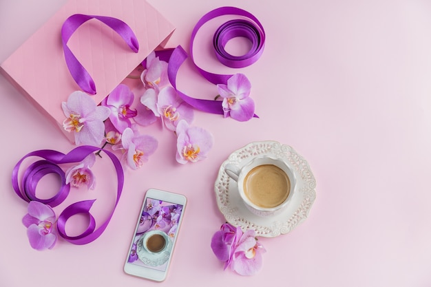 Top view of pink home office workspace with phone and coffee cup. social media flat lay with coffee, flowers and smartphone. female pink floral workplace
