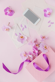 Top view of pink home office workspace with phone, letters, flowers and gift bag. social media flat lay with flowers, papers and smartphone. female pink floral workplace