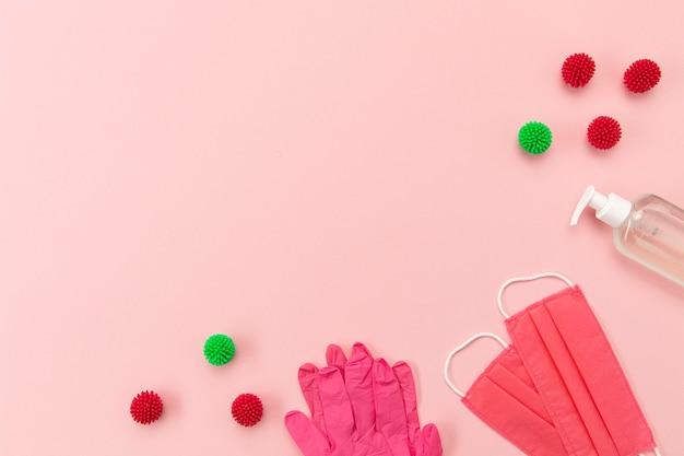 空白の電話とコピースペースを備えた上面ピンクの医療用マスクと手袋