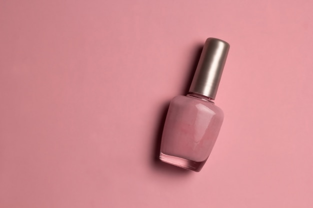 Top view pink nail polish on pink background