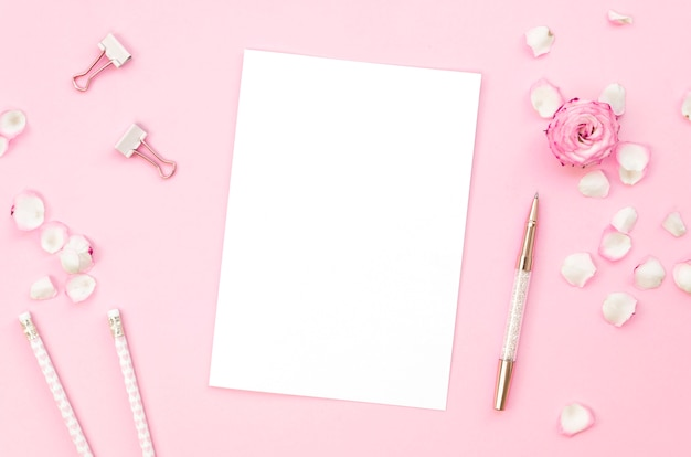 Top view of pink office supplies with rose petals