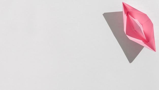 Вид сверху розовый бумажный кораблик