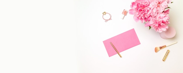 Top view of a pink paper envelope with a gold pen, womens accessories, a bouquet of pink peonies, candles isolated on white