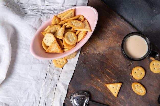 Вид сверху розовая тарелка, полная чипсов с молоком на сером фоне, цвет хрустящих крекеров