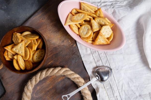 Вид сверху розовая тарелка, полная чипсов с веревками на сером фоне, цвет хрустящей закуски крекера