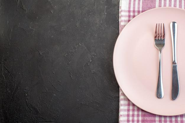 Вид сверху розовая тарелка с вилкой и ножом на темной поверхности