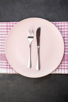 Top view pink plate with fork and knife on dark background