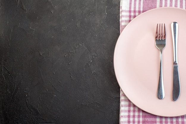 Top view pink plate with fork and knife on dark surface