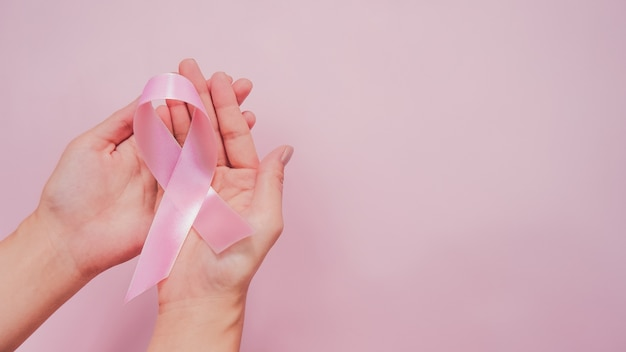 Top view of pink ribbon on adult hand