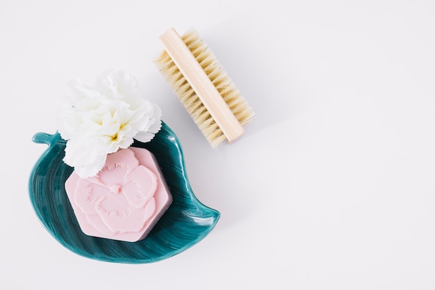 Top view of pink soap and flower on leaf shape plate near brush over white background
