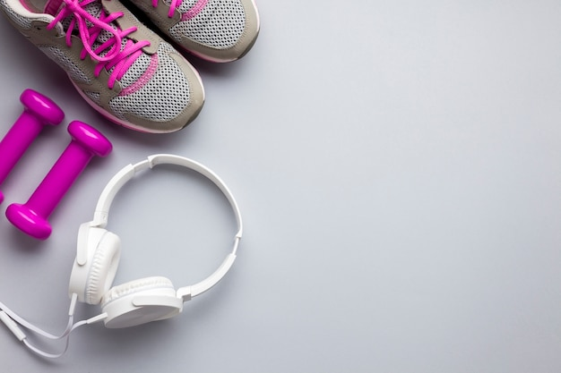 Top view pink sports attributes with headphones