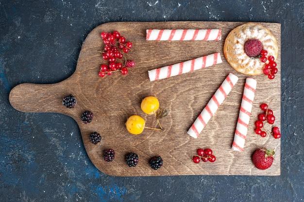 トップビューピンクの粘着性のあるキャンディーと暗い背景のベリーフルーツフルーツベリーキャンディー甘いグッディボンボン