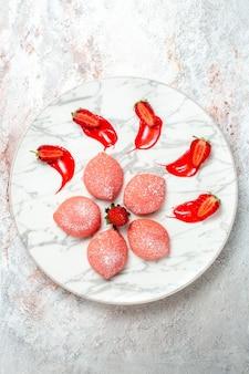 상위 뷰 핑크 딸기 케이크 흰색 배경에 작은 과자 케이크 쿠키 차 과일 비스킷 달콤한 설탕