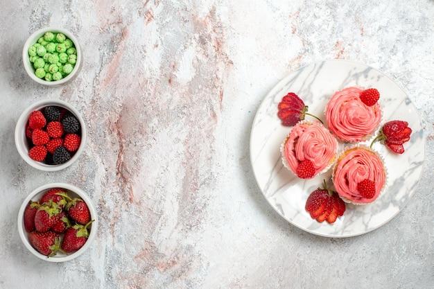 Vista dall'alto di torte alla fragola rosa con frutti di bosco sulla superficie bianca