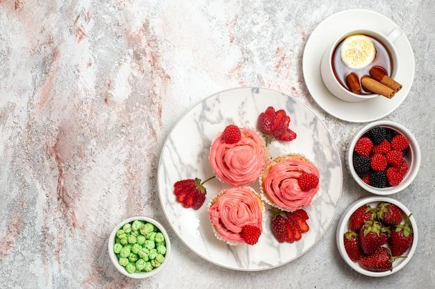 Vista dall'alto di torte di fragole rosa con confetture e tazza di tè sulla superficie bianca