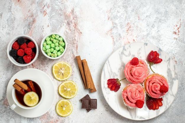 Vista dall'alto di torte di fragole rosa con confetture e tè sulla superficie bianca